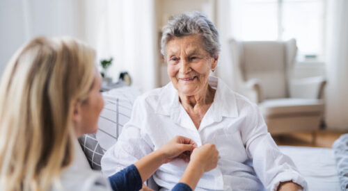 A young health visitor helping a happy sick senior woman sitting on bed at home.